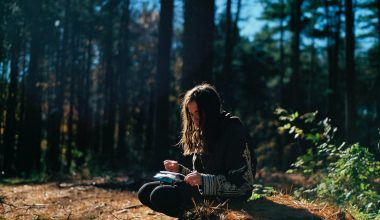 woman writing on a log in the woods